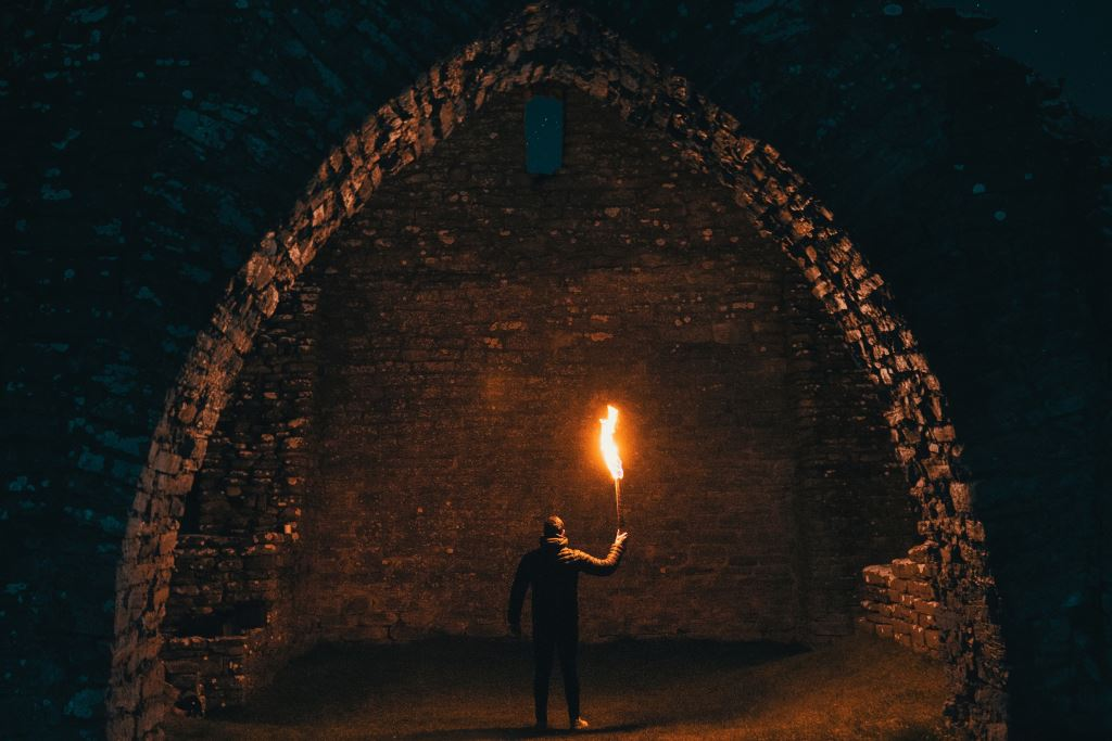 Man holding a flame-torch in a stone alcove